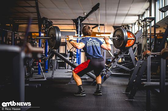 Spannung im gesamten Körper aufbauen und mit geradem Rücken gleichmäßig in die Hocke gehen. Bei der Abwärtsbewegung einatmen