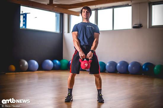 ... und in Endposition wieder aufrecht stehend, mit geradem Rücken das Gewicht aufheben. Dabei das Ausatmen nicht vergessen. Arme bleiben lang, Brust raus, Schultern zurück.