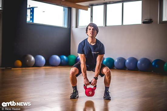 """Wer keine Langhantel zur Verfügung hat, kann die effiziente Übung auch mit der Kettlebell durchführen. In Ausgangsposition die Arme gerade zwischen den Beinen nach unten """"fallen"""" lassen..."""