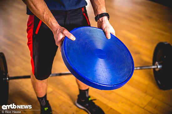 Wer der Übung etwas mehr Würze verleihen möchte, kann sich eine Balance-Scheibe dazu nehmen.