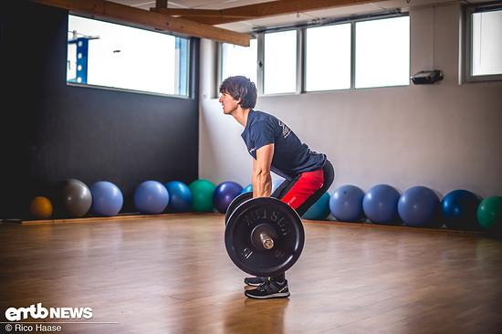 Ausgangsposition: Die Arme gerade nach unten hängen lassen und die Hantel an den Beinen entlang nach oben heben. Die Hauptbewegung erfolgt aus dem geraden Rücken, wobei sich die Beine nur wenig beugen. Beim Heben gleichmäßig ausatmen.