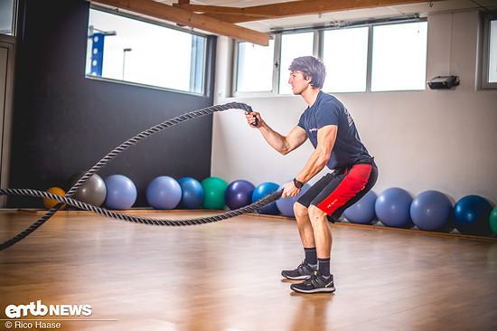 Auf festen, schulterbreiten Stand achten. Dabei leicht in die Knie gehen um stabil zu stehen, wenn es gleich los geht. Dann unter voller Körperspannung die Seile mit so viel Energie wie möglich zu einem abklingenden Sinus aufschleudern.