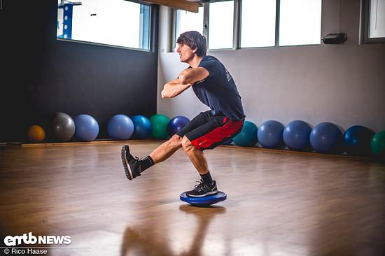 Weitere Möglichkeiten, um seine Balance mit der wackeligen Scheibe zu schulen, sind Kniebeugen.