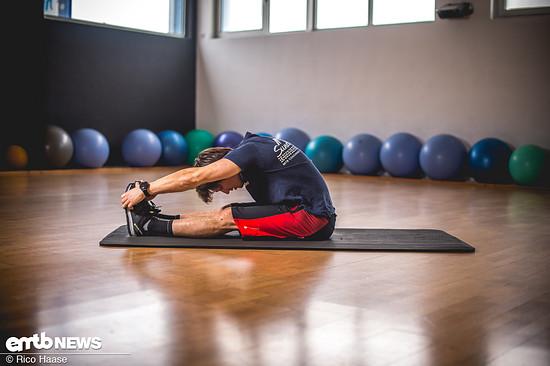 … und versuchen, mit den Armen an die Füße zu kommen. Dabei die Knie am Boden lassen und den Rücken möglichst gerade halten.