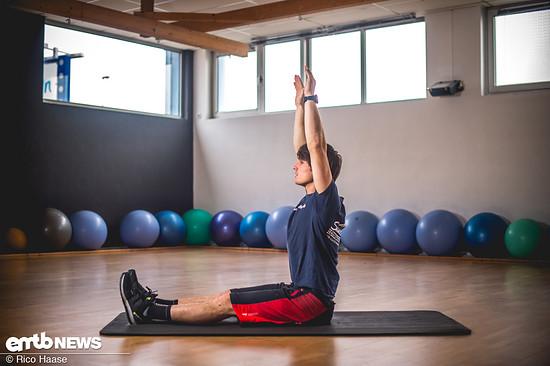 Um die Oberschenkelrückseite und den unteren Rücken zu dehnen, in Ausgangsposition aufrecht sitzen …